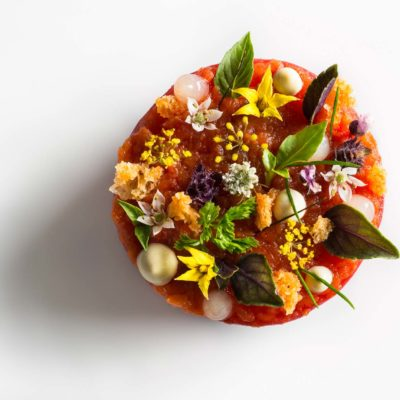 Tomato lobster disc garnished with croutons, chervil, chive tips, lemon gel, bonito mayonnaise, tomato flowers, fennel flowers, and basil on a white surface. Prepared by Daniel Humm at Eleven Madison Park.