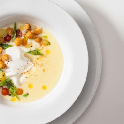 Cold potato and leak soup with yogurt, green beans, potatoes, currant tomatoes, croutons, extra virgin olive oil and hot pepper. Served on a white ceramic bowl on a white background.