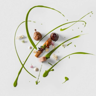 A quail leg with a rhubarb baton over a parsley coulis and puree with roasted and shaved artichokes and garnished with star anise and mini white and purple flowers prepared by Chef Christoph Zangeri of The Hotel Tannenhof in Austria.